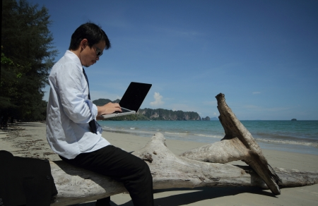 Business man sitting on a block of wood on the beach  photo