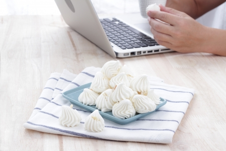 Man with laptop on meringue dessert was placed in a blue plate with a glass of tea  photo
