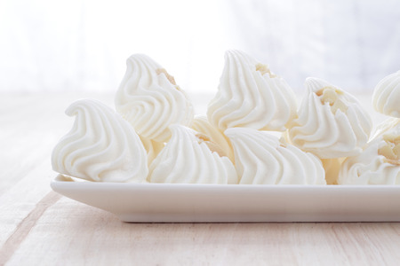 Meringue dessert placed in white dish on wooden table  photo