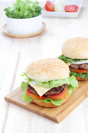 Two grilled homemade hamburgers on a wooden board in environment from the breakfast table  photo