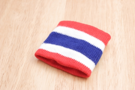wristbands: Wristbands striped flag of Thailand placed on a wooden table. Stock Photo
