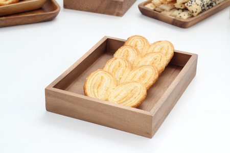 Puff pastry is placed in a wooden plate on white table  photo