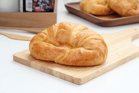 Croissant is placed in a wooden plate on white table  photo