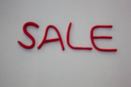 red clay: Sale sign made from red clay on white paper