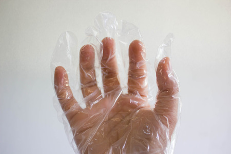 plastic glove: One hand with plastic glove on white background