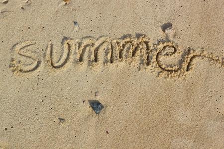 Handwritten the word summer on sand photo