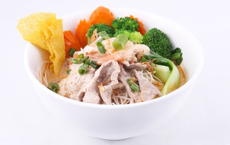 Laksa noodle soup with chicken, fresh vegetables and wonton  Stock Photo