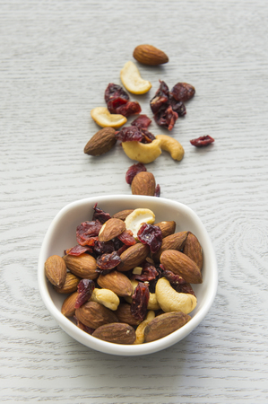 Mixed nuts in a bowl on a white wooden background. Stock Photo