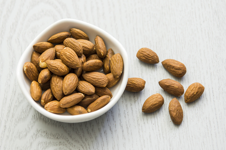 Almonds on wooden table. Almonds background. Group of almonds. Stock Photo