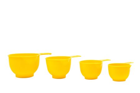 durable: Four measuring cups made of durable yellow plastic arranged in a row to iillustrate the progression in size.