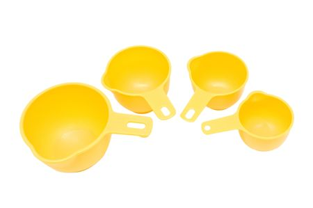 durable: Four measuring cups made of durable yellow plastic arranged in a semi-circle that illustrates the progression in size.