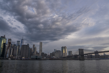 Amazing clouds over New York City skyline and Brooklyn Bridge on Hudson River