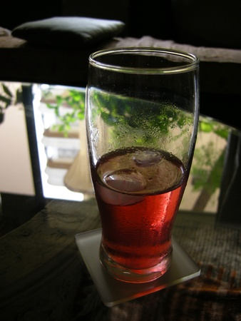 A refreshing glass of chilled red drink with ice, against the back light.