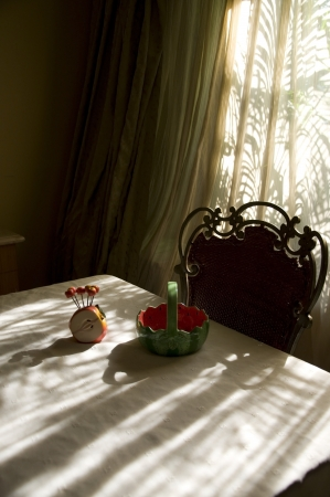 An artistic composition of a ceramic apple holder and a basket kept on the dinning table with chair
