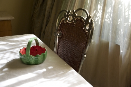 An artistic composition of a ceramic basket kept on the dinning table with chair Stock Photo