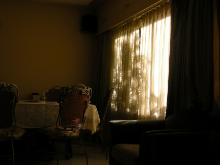 View of a room with the dim sun light coming through the transparent shades