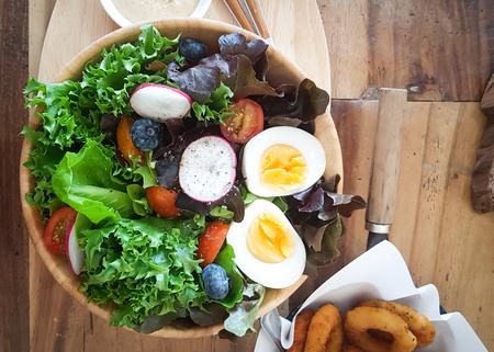 Vegetable Salad with Boiled Egg Slices in Wooden Bowl