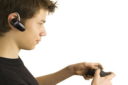 Teenage boy gaming intensely with wireless headset and gamepad