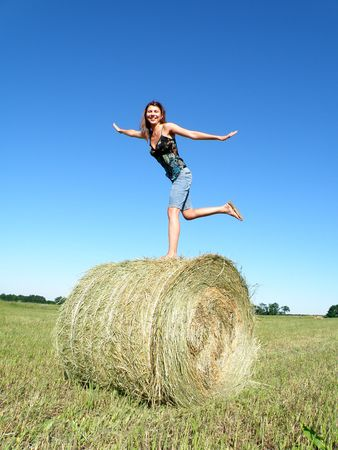 young girl costs on one foot on a hank of yellow hay     photo
