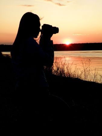 nature picture: The girl the photographer against a sunset does a nature picture