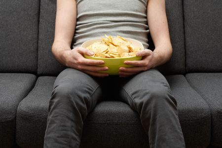 couch: A man on a couch eating potato chips