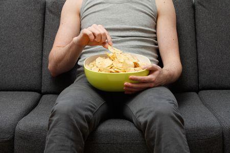 bored man: Un uomo su un divano a mangiare patatine fritte
