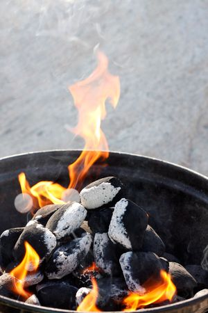 A grill with charcoal and flames photo