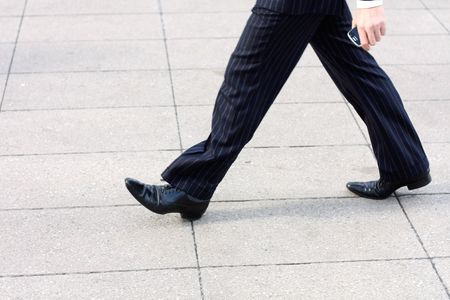 A business man walking with a phone in his hand Stock Photo - 5365803