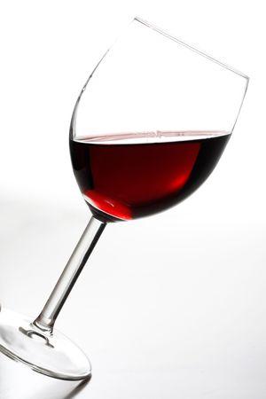 A tilted glass of red wine