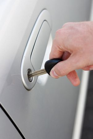 slot met sleuteltje: Een hand openen van een auto deur met een sleutel