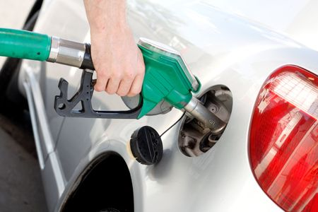 gas nozzle: A man pumping gas in to the tank