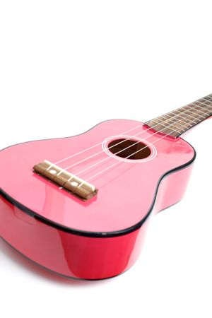 A small pink guitar isolated on white