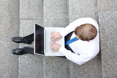 birds eye view: Business man sitting on stairs outdoor