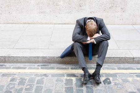hombre preocupado: Un hombre de negocios preocupados sentado en algunas escaleras