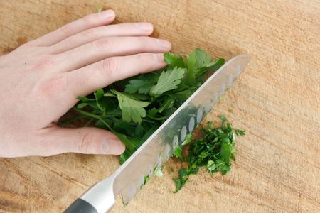 Chopping parsley on a wooden surface Stock Photo - 6115871