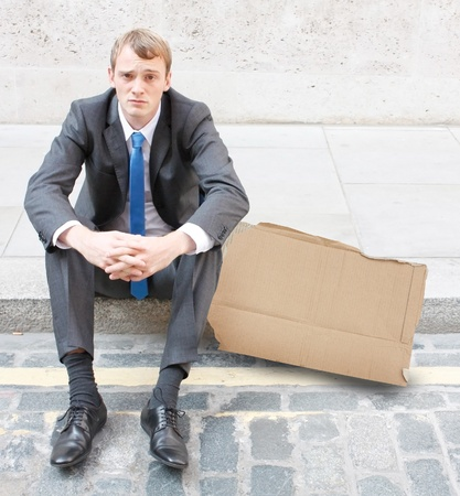 sacked: A worried business man sitting on some stairs Stock Photo