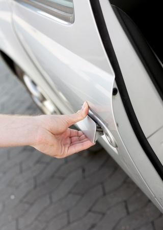 A hand opening the car door