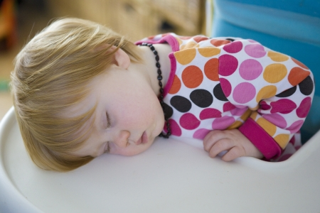 Red Haired Baby asleep on High Chair photo