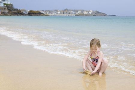 Young girl sitting on beach playing with sand