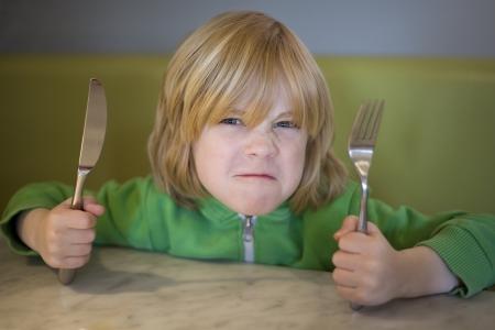 Jeune garçon vilain attente pour la nourriture avec un regard de moyenne sur son visage