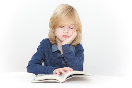 Young blonde boy reading a book photo