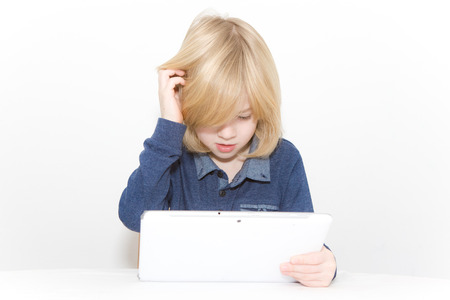 Young blonde boy playing on a tablet while scratching his head