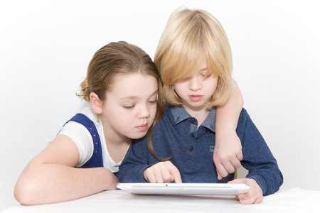 Brother and sister playing on a tablet Stock fotó