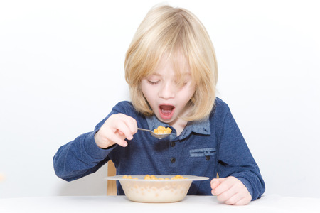 Young blonde boy eating breakfast