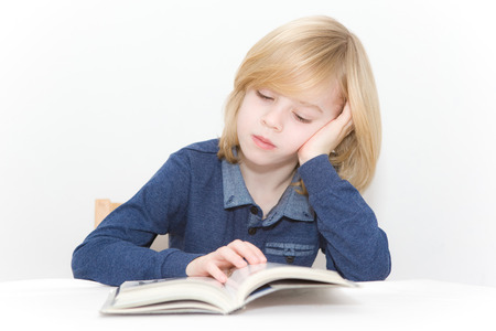 comprehension: Young blonde boy reading a book Stock Photo