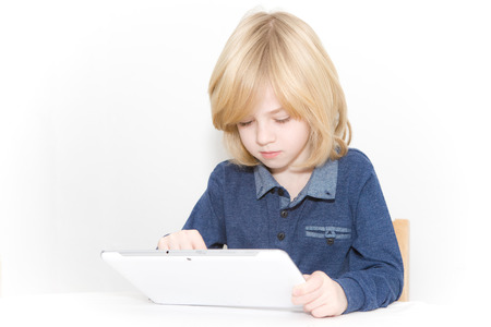 Young blonde boy playing on a tablet
