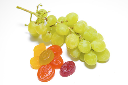 Green Grapes with Multi-Coloured Sweets on a White