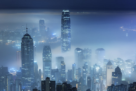 Misty night view of Victoria harbor in Hong Kong city Stock Photo