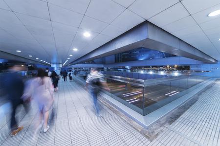Crowd of anonymous people walking in modern pedestrian walkway Stock Photo