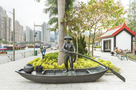 Hong Kong, China -  February 02, 2017 : statue of fisherman and fishing boat parked at the storm shelter of Aberdeen fishing village in Hong Kong